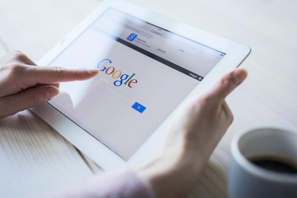 Gros plan sur une tablette tenue par une personne qui s'apprête à réaliser une recherche sur Google