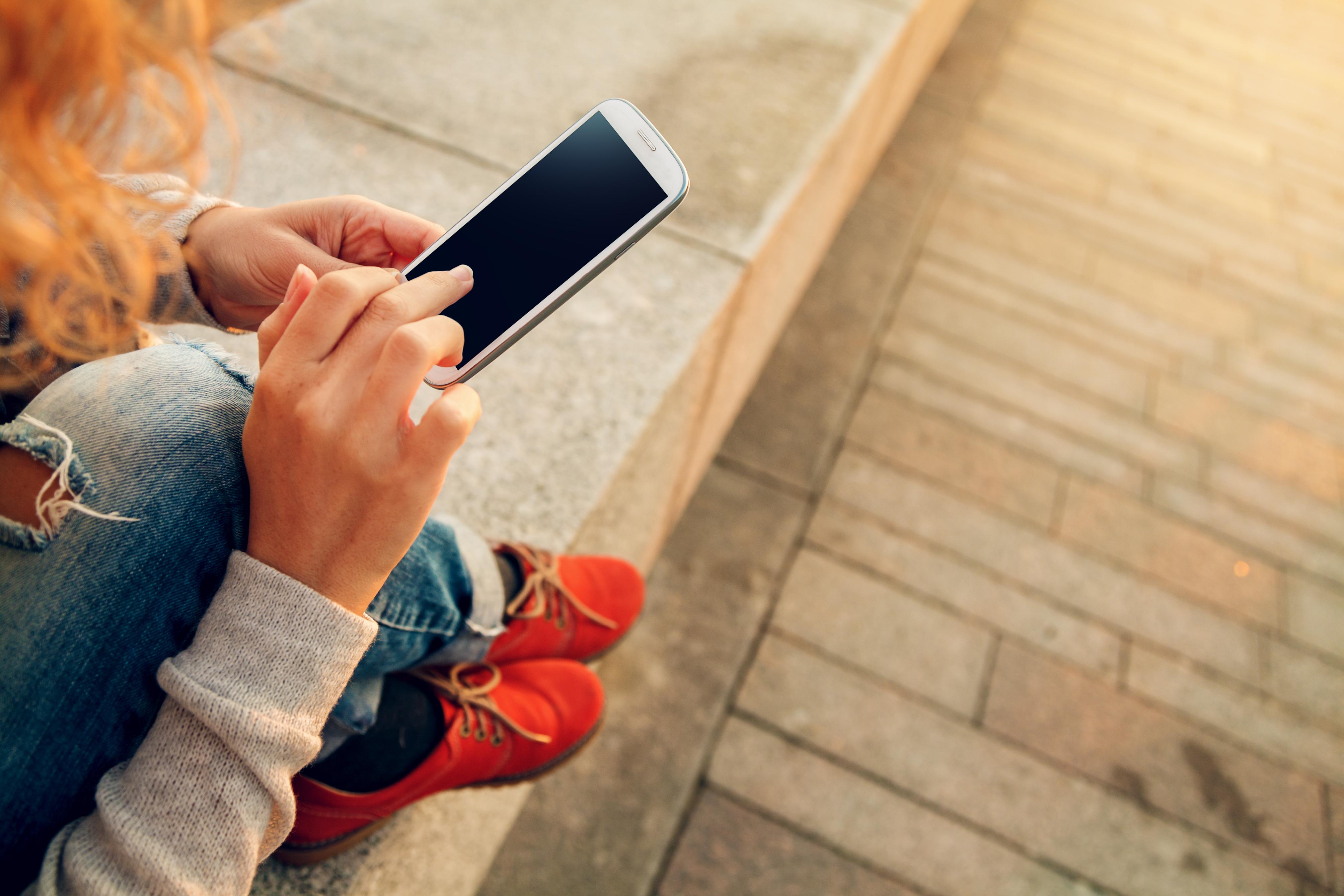 Jeune femme assise sur un muret utilisant un smartphone - Gros plan sur ses mains